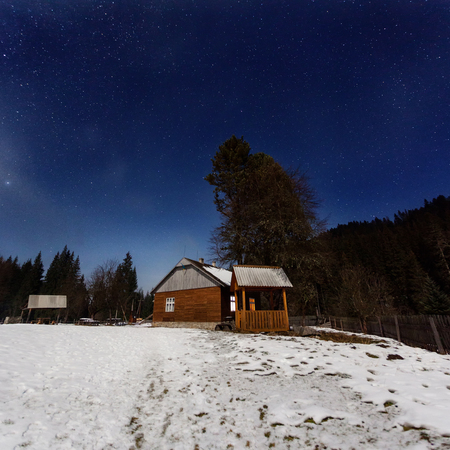 Small wooden house in the Ukrainian Carpathians, on the background of the winter forest at night