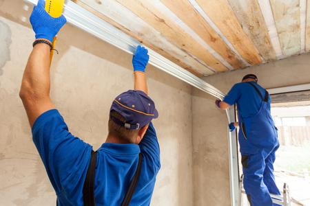 Installation de portes de garage. Les travailleurs qui installent l'installation et l'assemblage du rail de poteau et du ressort. Banque d'images - 85889042