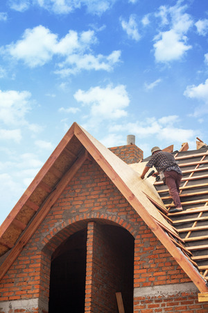 new addition: House under construction. Workers installing fibreboard on the roof Stock Photo