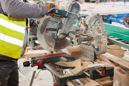 cut off saw: Framing contractor using a circular cut off saw to trim wood studs to length. Stock Photo