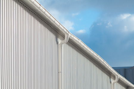 New white rain gutter on a building with white metal sheet against blue sky Standard-Bild