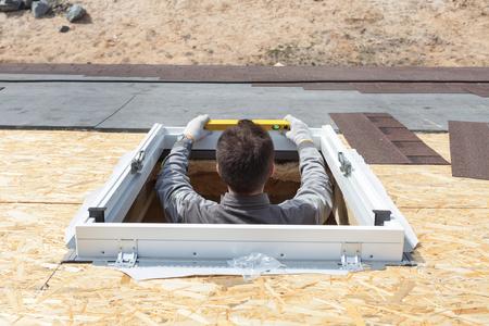 Worker on a asphalt shingle roof installing new plastic (mansard) or skylight  window Archivio Fotografico
