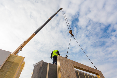 Roofer builder worker with crane installing structural Insulated Panels SIP. Building new frame energy-efficient house Stock Photo
