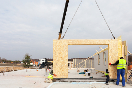 Roofer builder workers with crane installing structural Insulated Panels SIP. Building new frame energy-efficient house Stock Photo