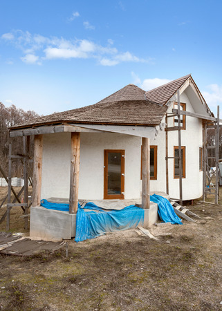 Construction of  adobe house with  thatched roof and plastic windows Stock Photo