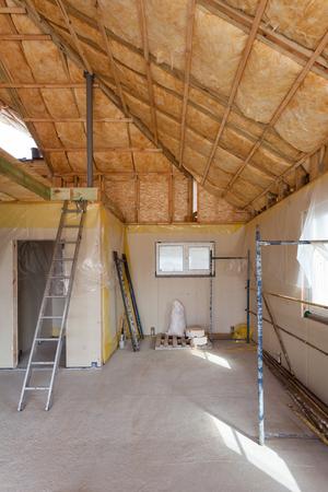 Een kamer in een nieuw gebouwde woning wordt besproeid met vloeibaar isolatieschuim Stockfoto