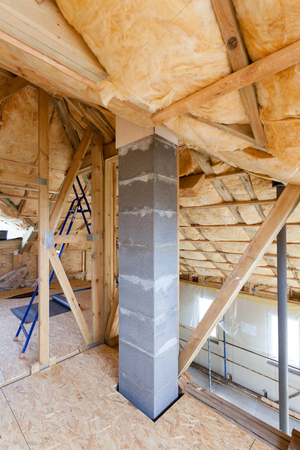 Iinsulation of attic with fiberglass cold barrier and insulation material Stock Photo
