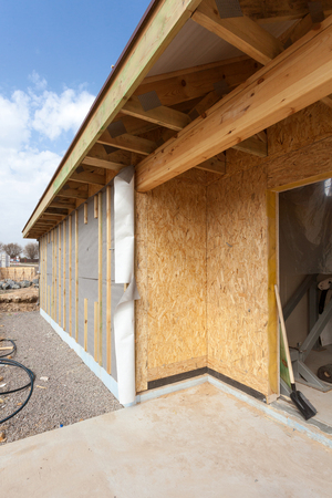 Modern frame energy efficient house under construction with membrane coverings, roof shingles and insulation materials Stock Photo