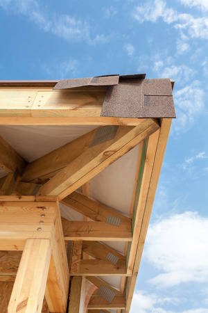 Corner of house with eaves, wooden beams and roof asphalt shingles Stock Photo