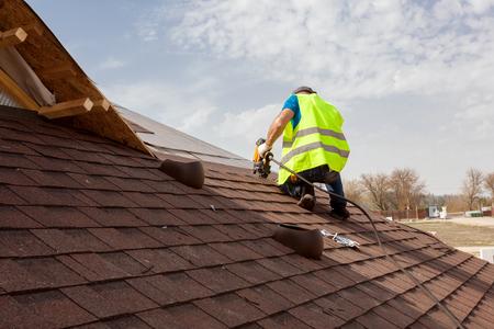 Pracownik budowlany kładący asfaltowe pokrycie dachowe (gonty) za pomocą gwoździarki na dużym osiedlu komercyjnym Zdjęcie Seryjne