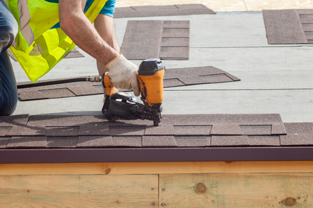Construction worker putting the asphalt roofing (shingles) with nail gun on a new frame house Stock Photo