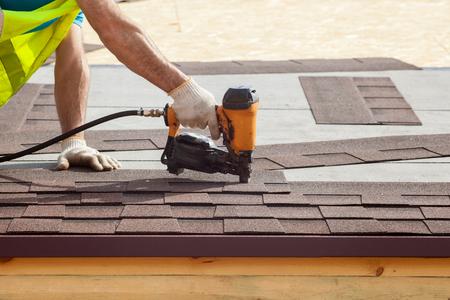 Pracownik budowlany kładący asfaltowe pokrycie dachowe (gonty) za pomocą pistoletu do gwoździ na nowy dom szkieletowy