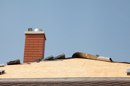 Roof with chimney made with red bricks, shingles and Plywood Boards