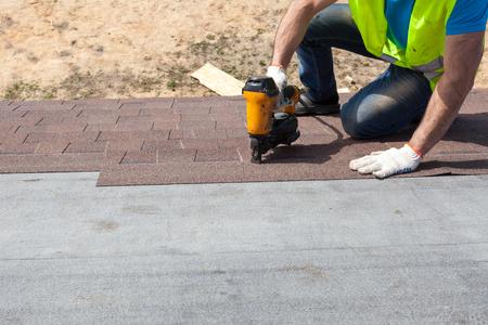 Roofer builder worker with nailgun installing Asphalt Shingles or Bitumen Tiles on a new house under construction Imagens - 88263047