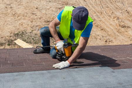 新居建設中にアスファルト鉄片または瀝青タイルをインストール nailgun の屋根葺き職人ビルダー ワーカー