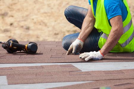Dekarz budowniczy pracownik z nailgun instalowanie gontów asfaltowych lub płyt bitumicznych na nowy dom w budowie