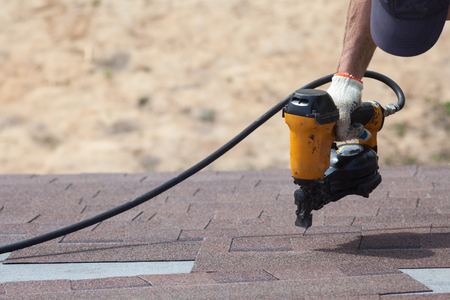 Roofer builder worker with nailgun installing Asphalt Shingles or Bitumen Tiles on a new house under construction