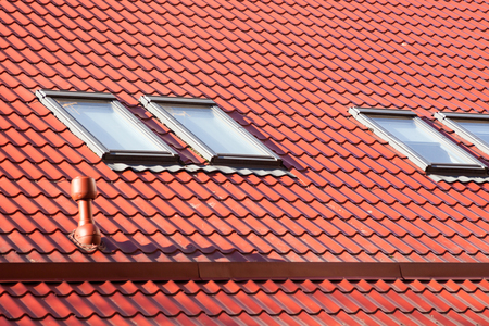 light slate gray: New red metal roof with skylights and Ventilation pipe for heat control Stock Photo