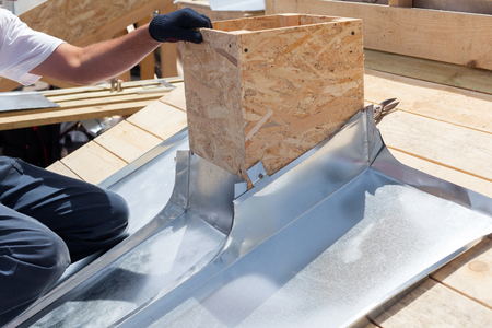 Roofer builder worker attach metal sheet to the chimney Standard-Bild