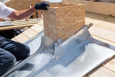 Roofer builder worker attach metal sheet to the chimney Banque d'images