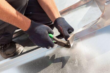 折り畳み式の大型フラット グリップと特殊なペンチを使用して金属板仕上げの屋根葺き職人ビルダー ワーカー