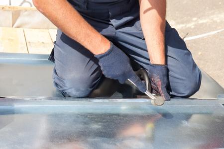 Trabajador constructor de techos acabado doblando una chapa de metal con mazo de goma