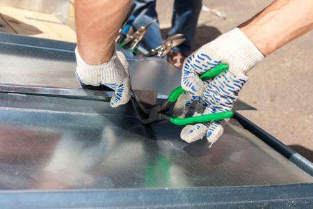 Couvreur pliant une feuille métallique en utilisant des pinces chimiques avec une grande poignée plate Banque d'images - 88649449
