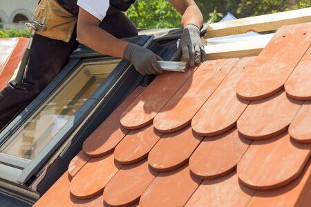 자연 지붕 타일 instaalation입니다. Roofer 작성기 작업자 사용 규칙 타일 사이의 거리를 측정합니다. 지붕창은 창문이 있습니다. 스톡 콘텐츠