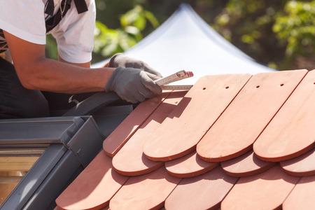 fibra de vidrio: Instalacion de tejas naturales Trabajador constructor de Roofer usa ruller para medir la distancia entre las baldosas