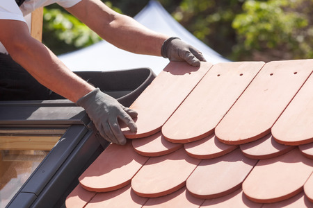 Ręki dacharz kłaść płytkę na dachu. Instalowanie naturalnej czerwonej płytki.