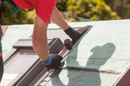Roofer installs metal profile on a roof window with a rubber mallet Imagens