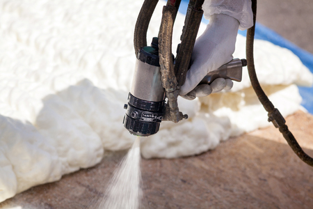 Technician spraying foam insulation using Plural Component Spray Gun Banco de Imagens - 88575699
