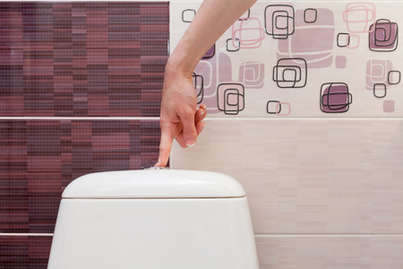 empty the bowel: Finger pushing button and flushing toilet. Stock Photo