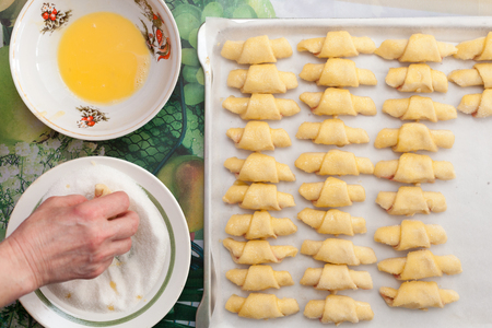 galletas integrales: Process of cooking small croissants with cherry for breakfast. Preparation of baking on a rustic white background. Egg-based breading. Breaded with sugar Foto de archivo