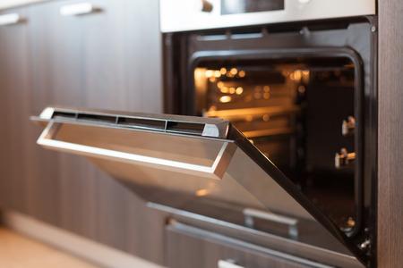 熱気の換気が付いている空の開いた電気オーブン。新しいオーブン。ドアが開いていて、ライトが点灯している 写真素材