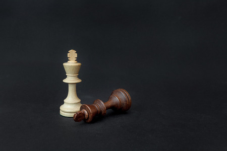 Chess game. White and black king challenging for victory. Isolated on black background.