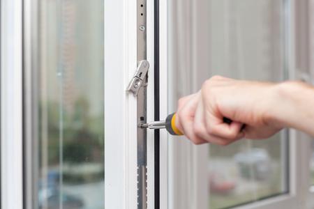 Handyman repairs plastic window with screwdriver. Zdjęcie Seryjne