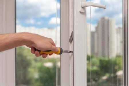 Handyman repairs plastic window with screwdriver