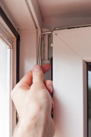 Handyman repairs plastic window with a hexagon. Workman adjusts the operation of the plastic window. 스톡 콘텐츠