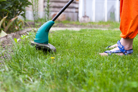 Garden equipment. Woman mowing the grass with a trimmer Stock Photo