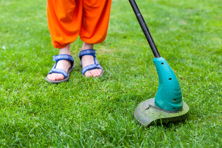 Garden equipment. Young woman mowing the grass with a trimmer Stock Photo