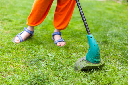 Gasoline lawn trimmer mows juicy green grass on a lawn on a sunny summer day. Close-up selective focus image. Garden equipment. Young woman mowing the grass with a trimmer. Stock Photo - 92630156