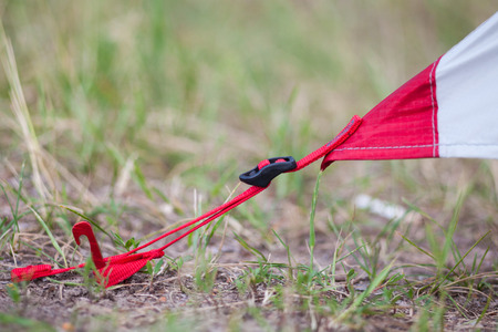 Placement of red camping tent, macro shot of peg and grass Stock Photo