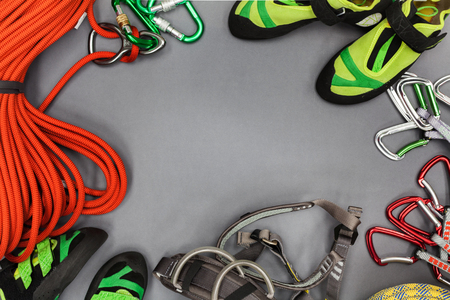 Climbing equipment laid out on on a black background. Rope, climbing shoes, chalk bag, quickdraws, belay, rappel device with carabiner, and other