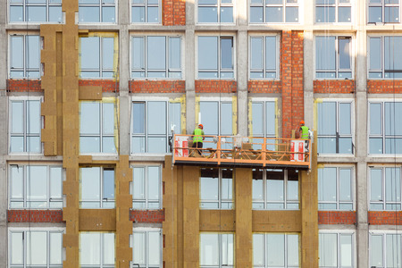 High-altitude work on the external walls of high-rise building. Glass wool insulation. The worker insulates the house standing on the scaffolding Zdjęcie Seryjne