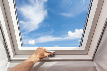 Man close new skylight (mansard window) in an attic room against blue sky Stock Photo