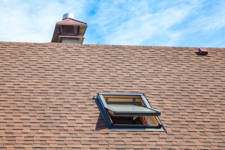 New roof with skylight, asphalt roofing (shingles) and chimney. Roof with mansard windows .