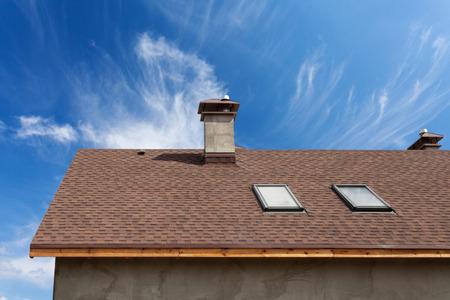 Nowy dach ze świetlikiem, pokryciem asfaltowym (gontem) i kominem. Dach z oknami mansardowymi. Zdjęcie Seryjne