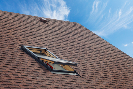 Roof with mansard windows and asphalt shingles.Open skylight on a roof shingles under construction Standard-Bild
