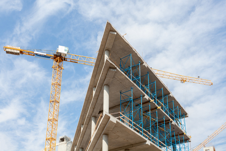 High-rise building under construction. The site with cranes against blue sky.